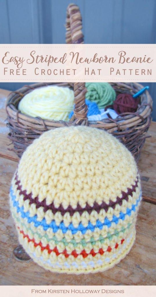 A yellow crochet hat with stripes sits on a wooden bench in front of a basket of yarn and crocheting supplies.