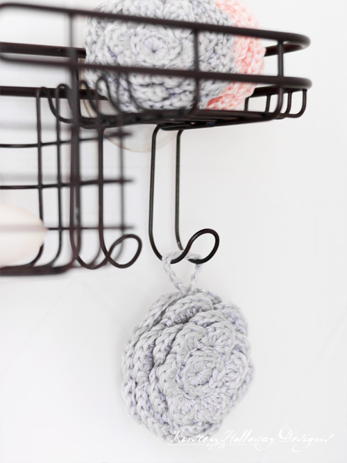 Crochet face scrubies/makeup remover pads hanging on a shower rack.