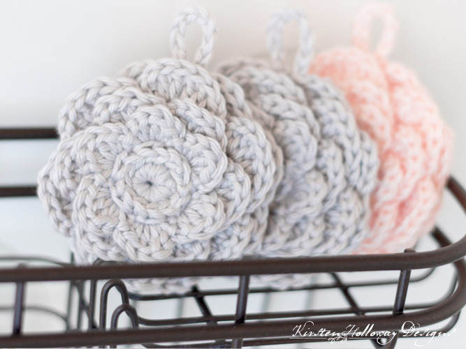 Close-up of flower-shaped crochet scrubbies sitting on a shower rack.