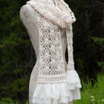 A beautiful lacy summer scarf with flowers and ruffles sewed to the ends.