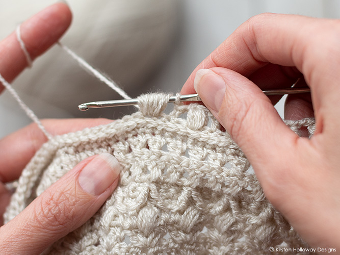 Crocheting puff stitches for the classic baby bonnet.